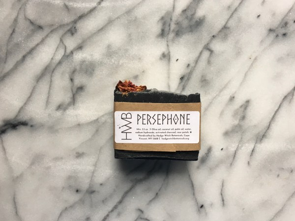 One bar of Persephone charcoal soap with wrapping and label on a marble background