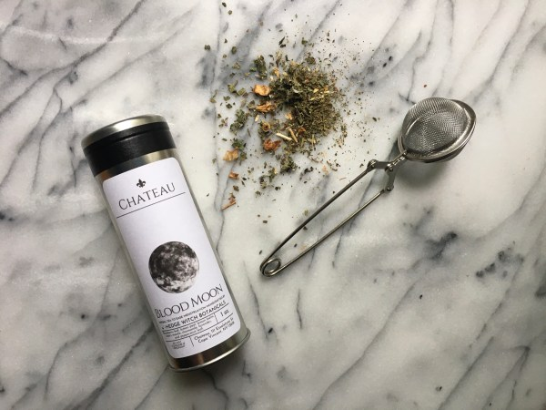 A tin of Blood Moon Tea on a marble background with tea infuser and loose tea leaves