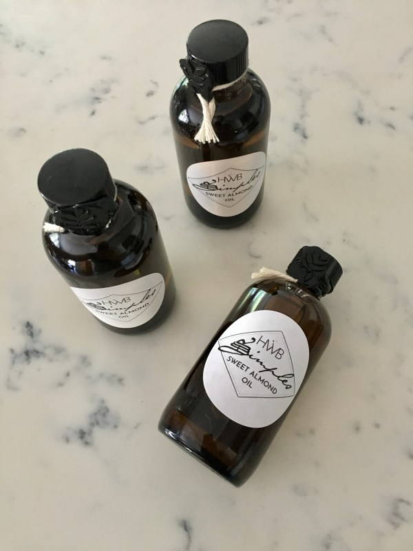 3 amber glass bottles with white labels, containing sweet almond oil