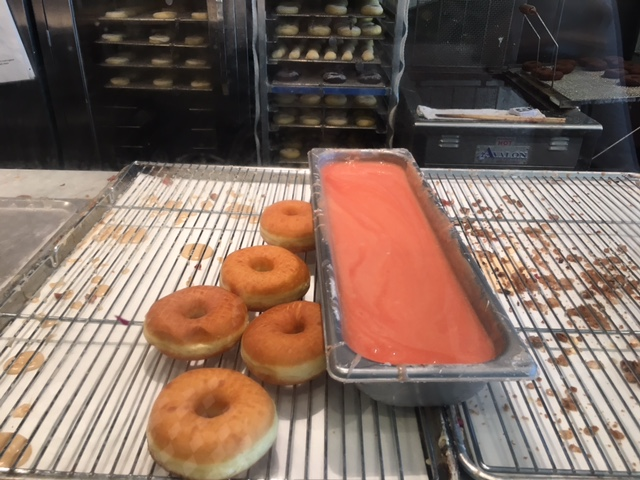 Sidecar Doughnuts about to be glazed