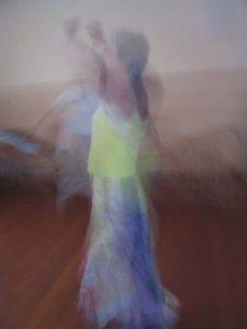 dansende vrouw, geel topje armen omhoog