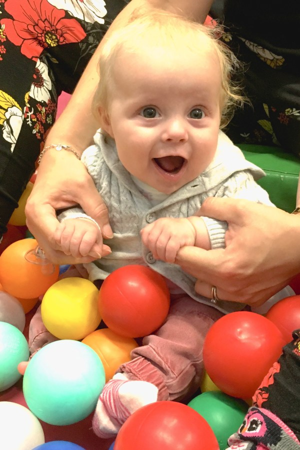 Baby sitting in ball pit with excited expression, holding onto the hands of the mother, who is sitting behind her