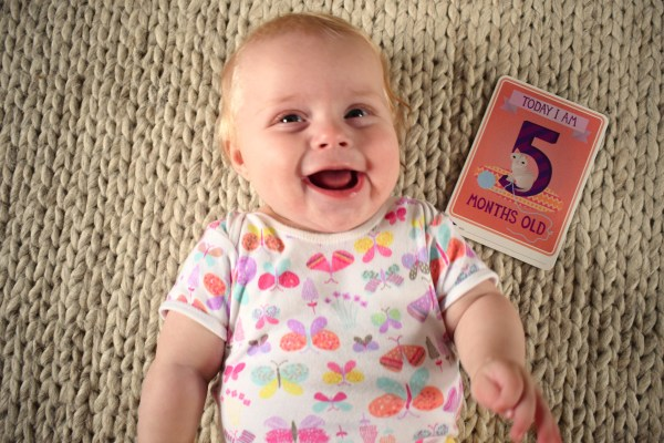 Baby lying on her back, smiling, with a card next to her, which reads, 'today I am five months old'