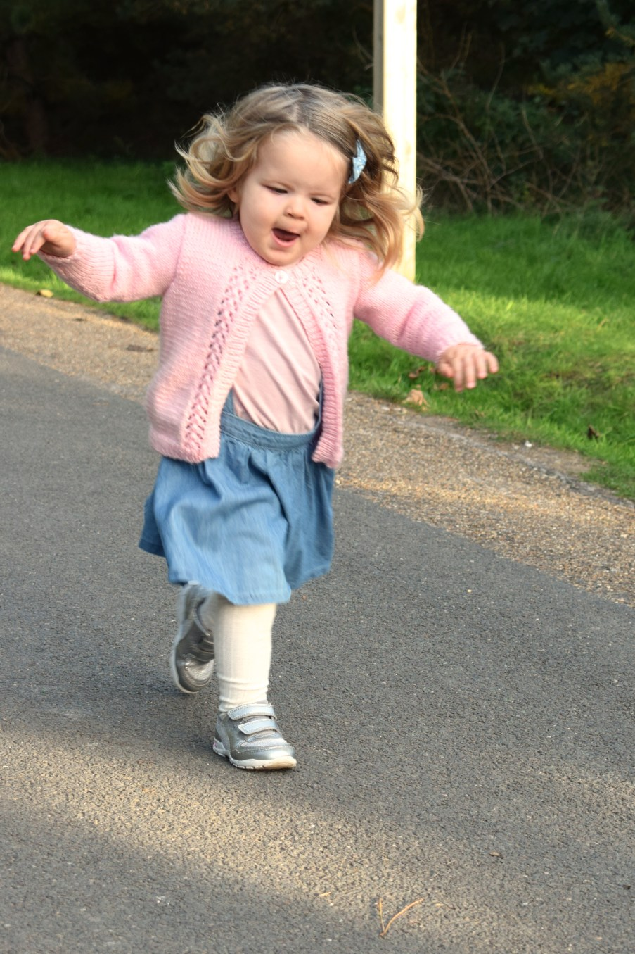two and a half year old girl running down a path with arms outstretched, smiling, in pink cardigan and blue dress