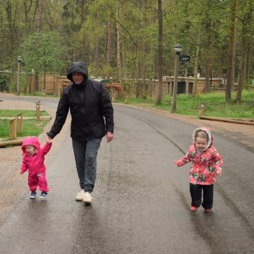 Dad and two daughters on rainy walk at Center Parcs Elveden Forest