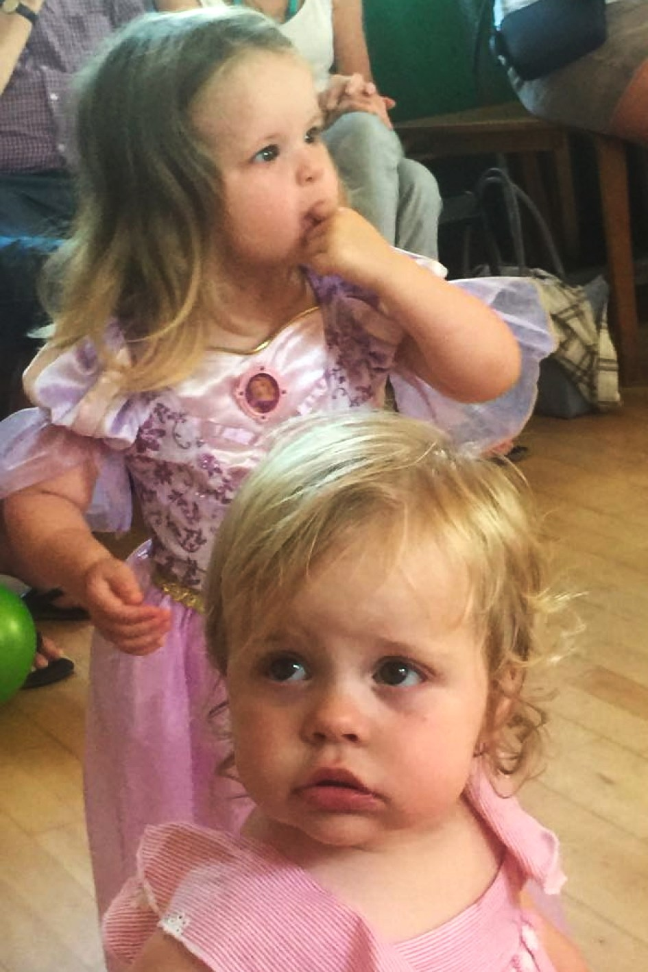 Two and one year old sisters at a party, dressed in pink