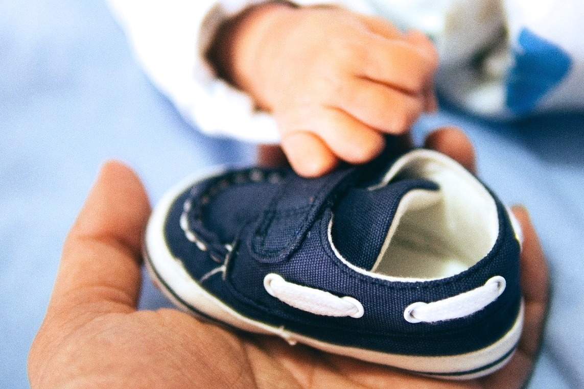 adult hand holding baby shoe next to baby's hands