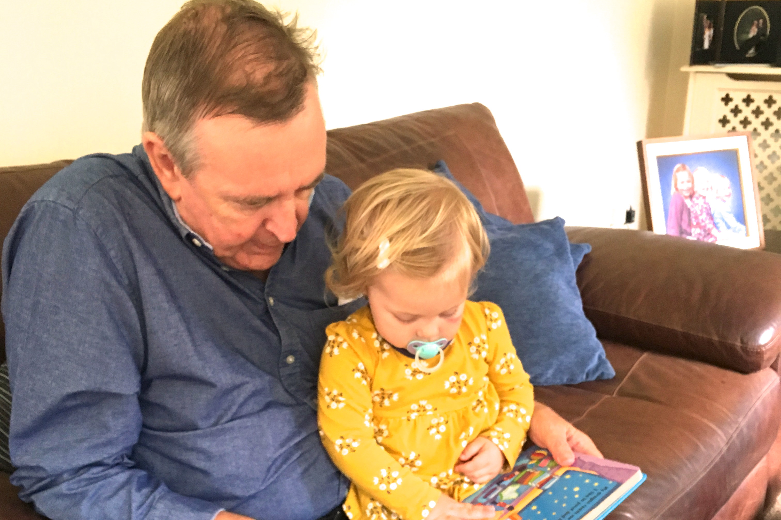 18 month old sitting on grandad's lap reading