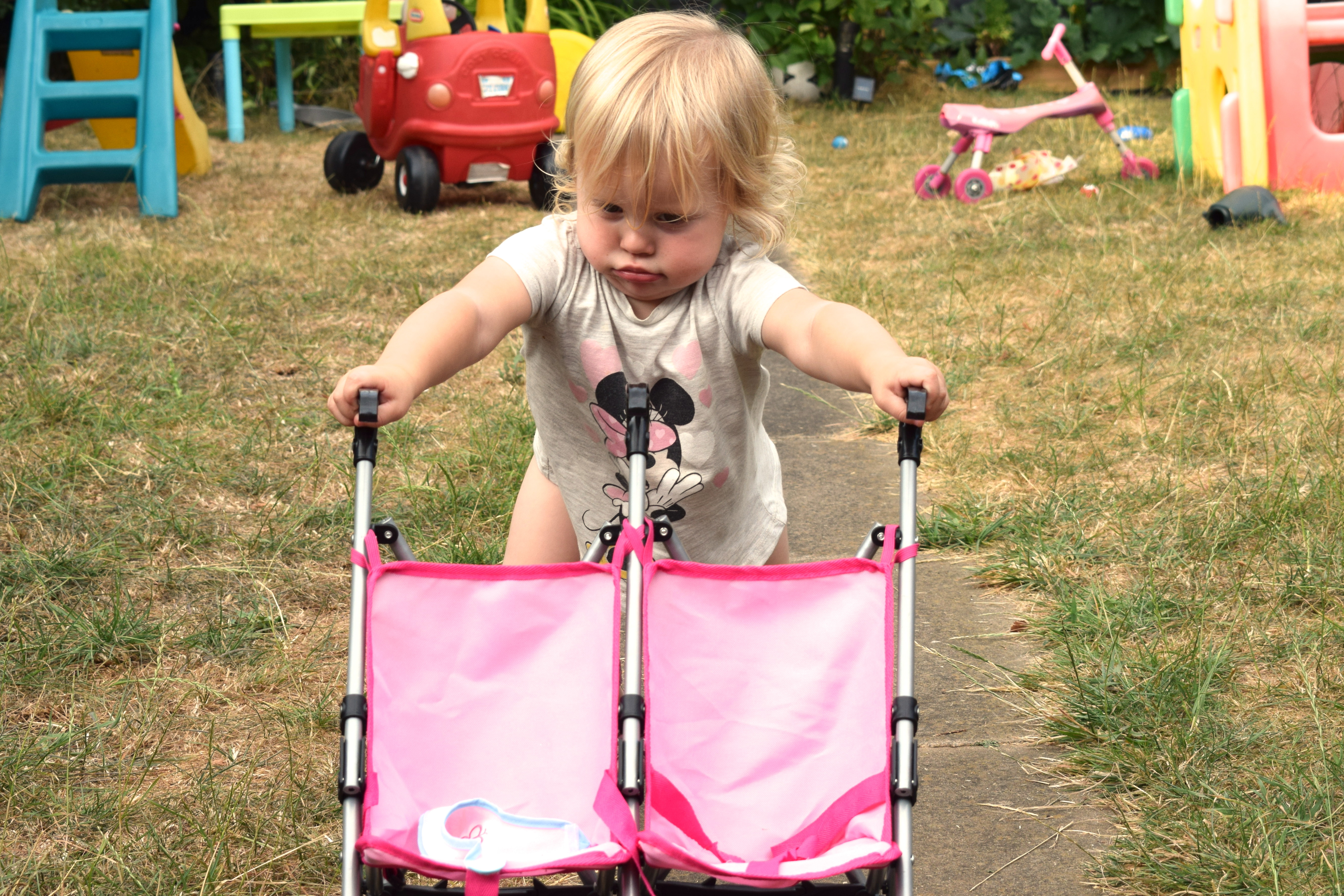 18 month old girl, pushing doll buggy up the garden path