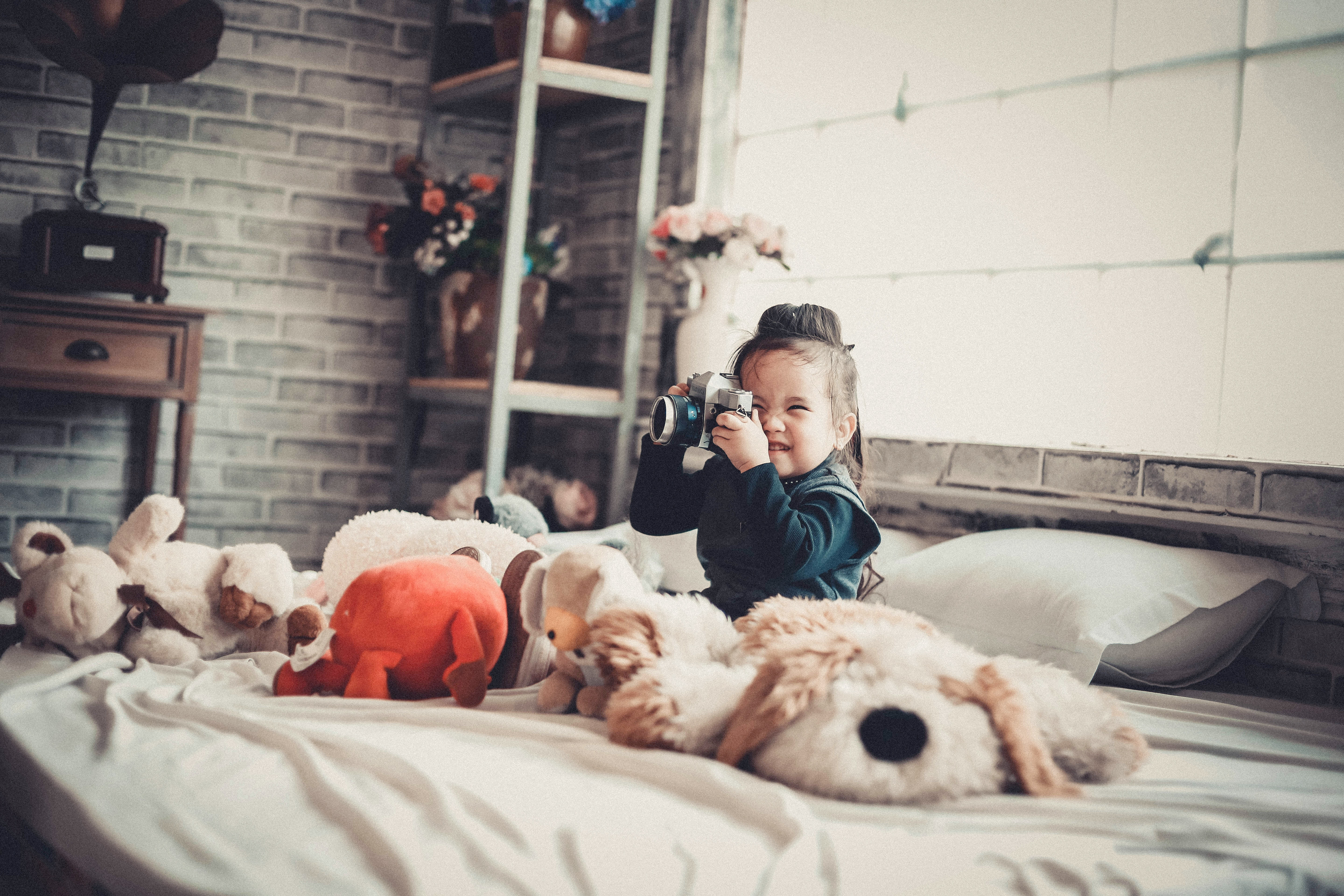 toddler girl, sitting on bed with cuddly toys, taking a photograph - when kids share a room