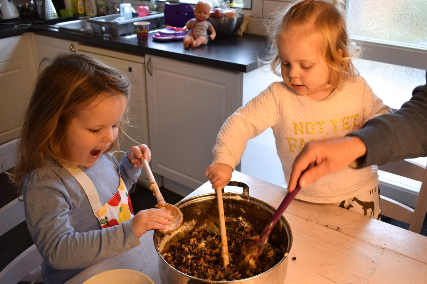 Two sisters at a dining room table, stirring up a Christmas cake mix with wooden spoons