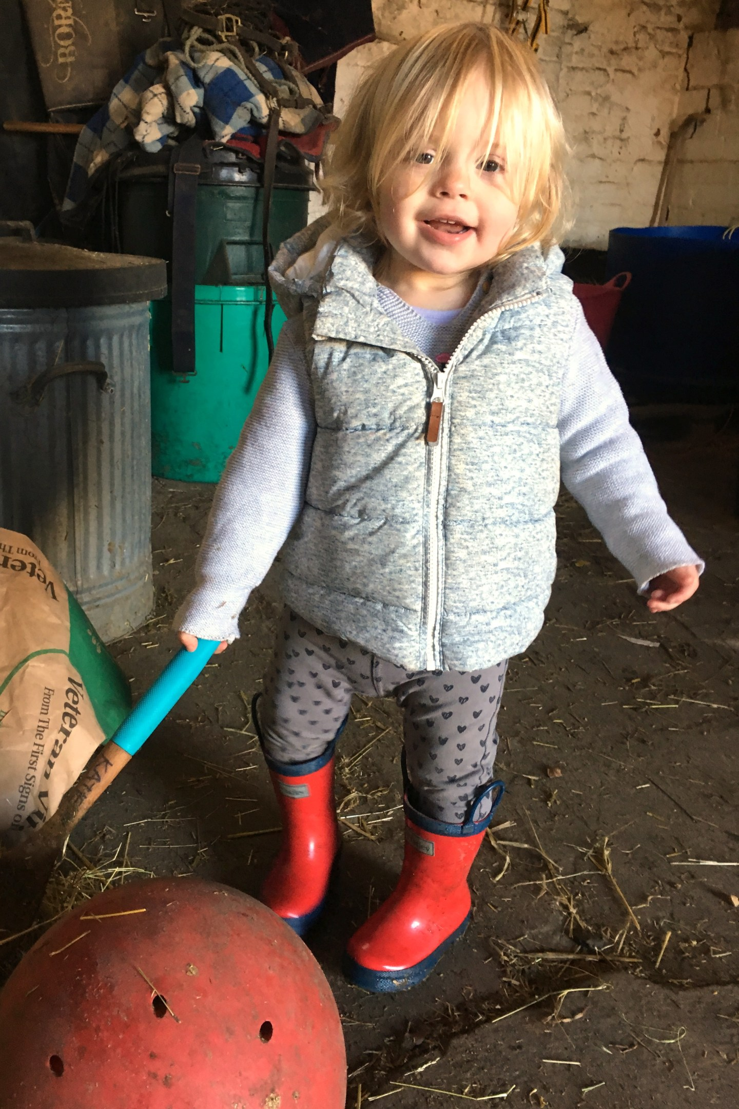 22 months old girl, helping make feeds at the stables
