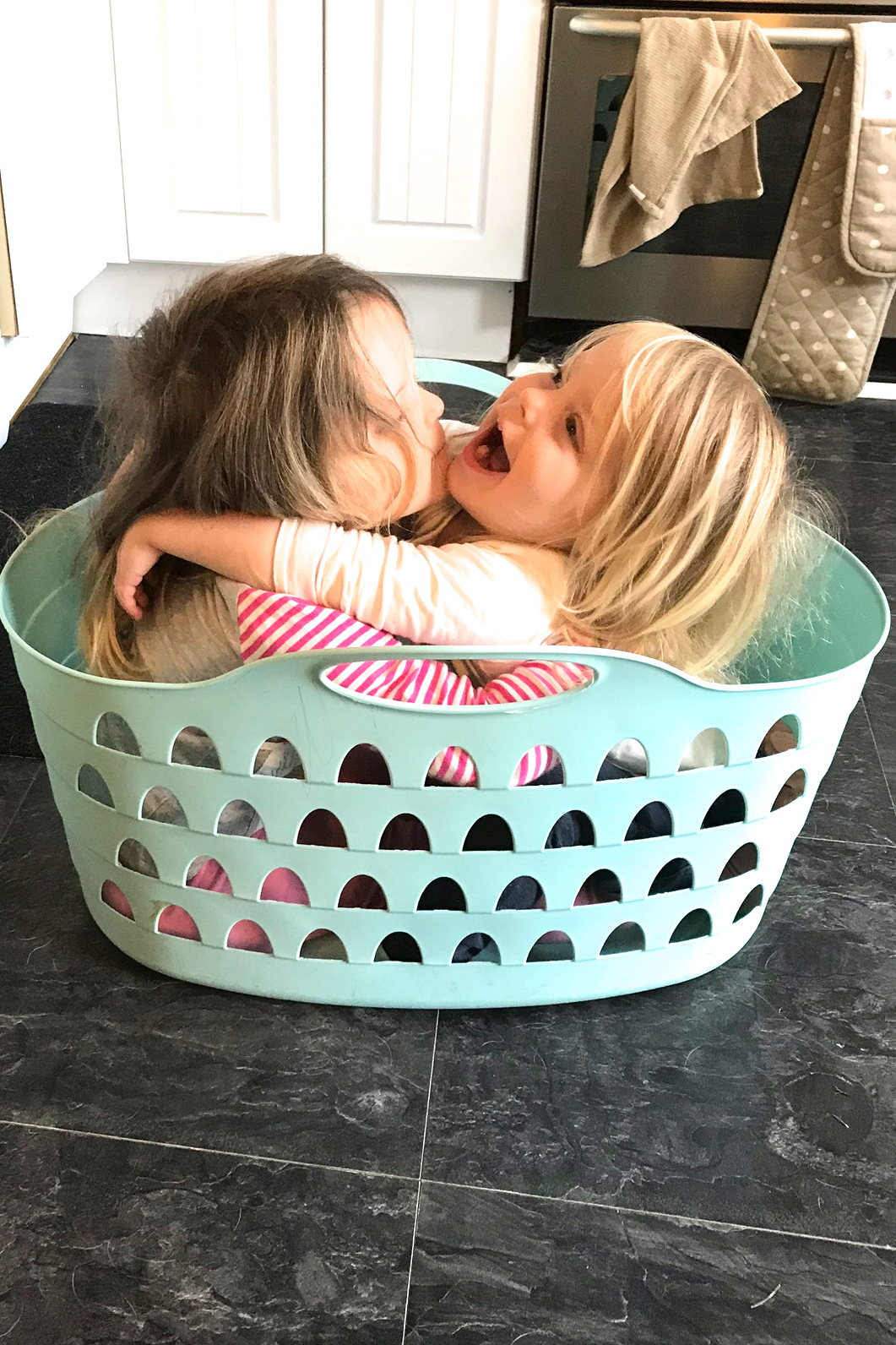 two sisters sitting in a washing basket, cuddling