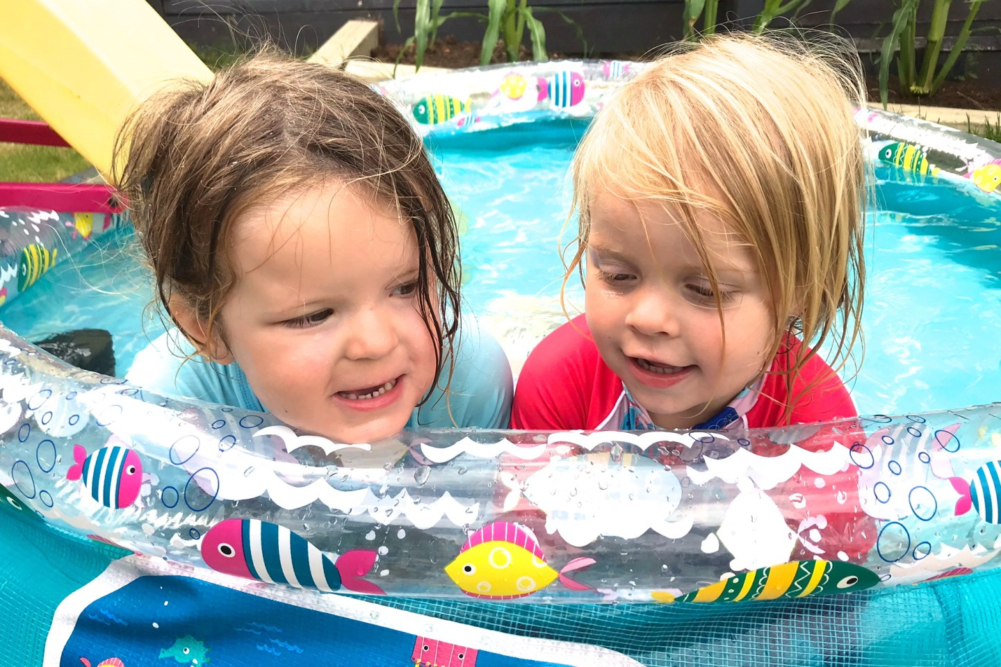 two sisters in a paddling pool