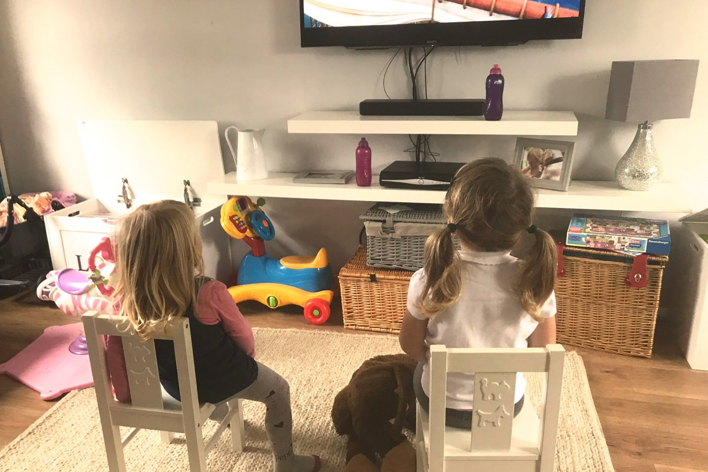 Two sisters, sitting side by side on chairs, watching TV