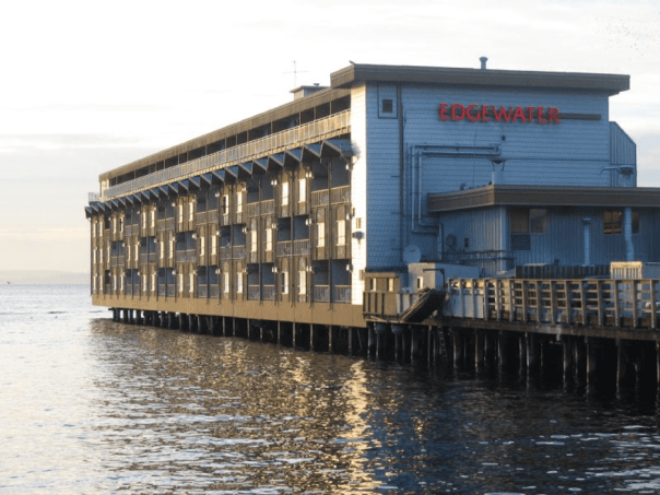 The exterior of the Edgewater hotel, sitting on a pier, with water in the foreground