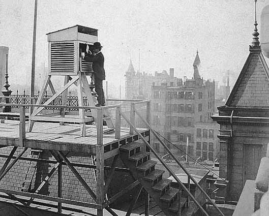 black and white photograph of a man taking weather readings from the roof of the Minneapolis post office