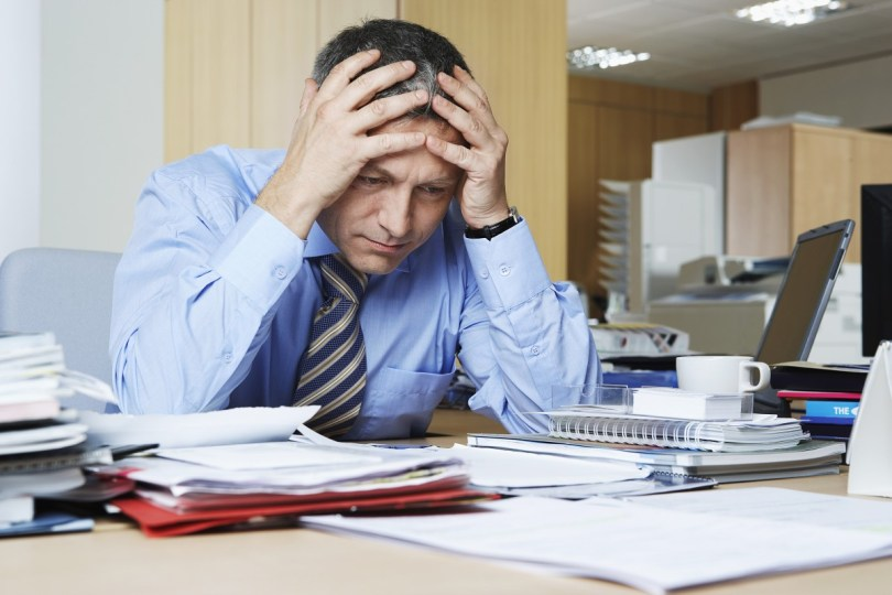 bigstock Frustrated middle aged busines 48603083 - Frustrated middle aged businessman sitting at office desk