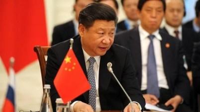 Xi Jinping an Tisch mit Wimpel der VR China