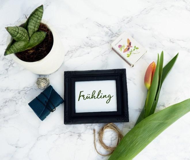 Flatlay mit Frühlingsaccessoires und Bilderrahmen zum Thema Achtsamkeit