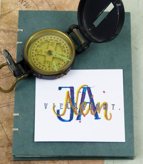 Kompass auf Buch mit Handlettering