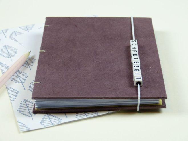 Notizbuch mit Gummiband und dem Wort Schreibzeit