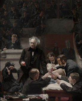man lecturing while men cut into someone with a scalpel