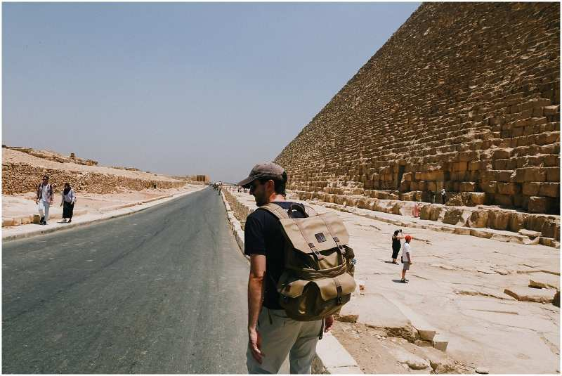 backpacker man next to pyramids of Giza in Egypt