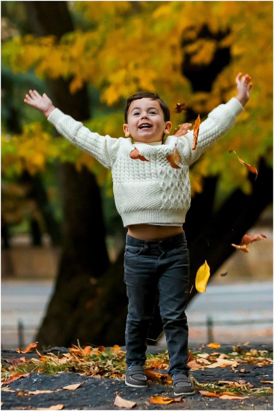 Helena Woods photographing kid jumping in autumn foilage