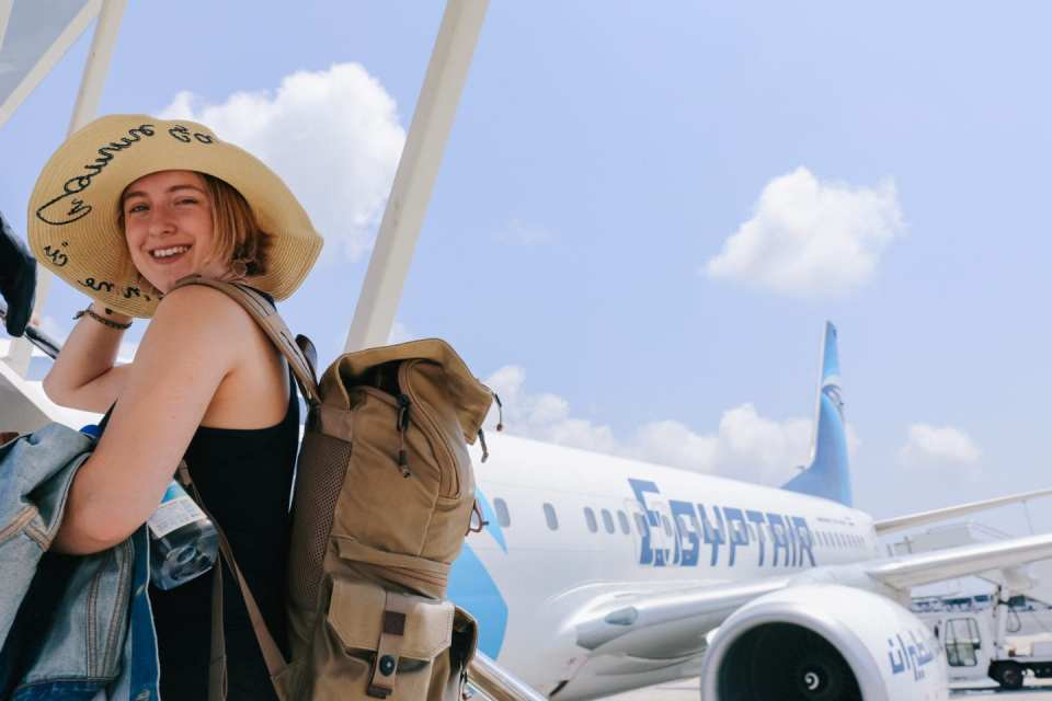 Egypt Air girl with sunhat and backpack boarding plane to Egypt