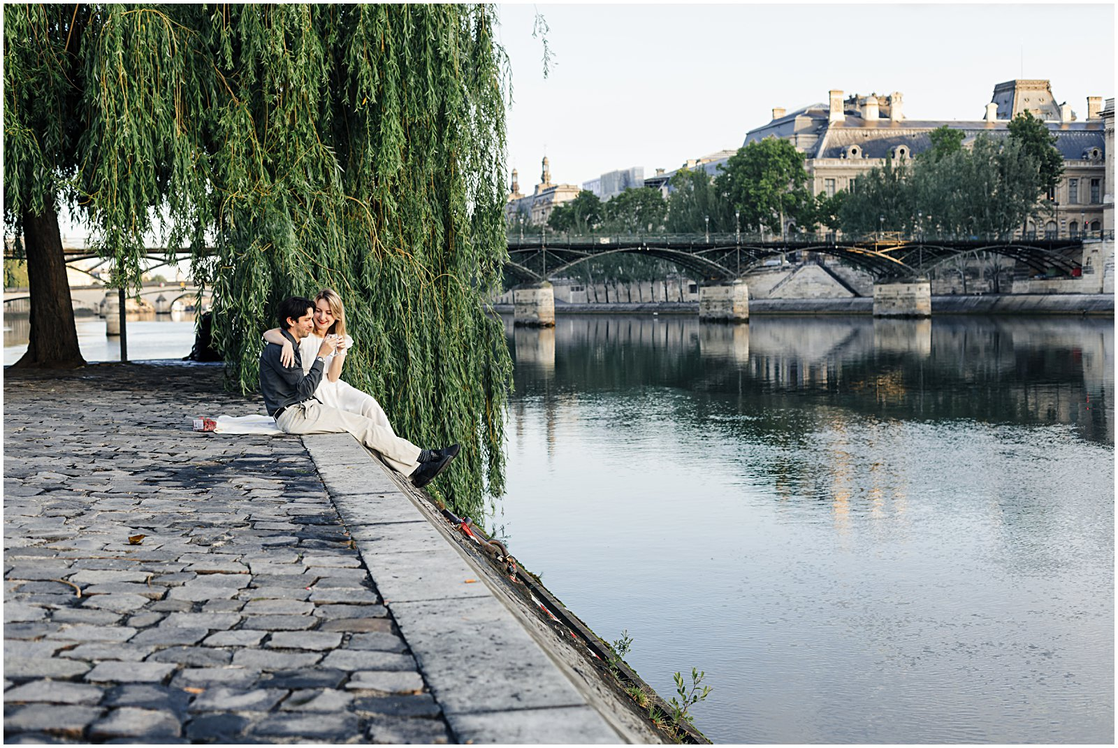 couple picnicing along the Pont Neuf willow tree in Paris