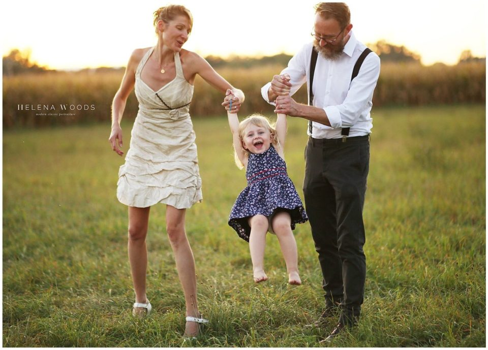 family holding toddler laughing photography by Helena Woods Photography