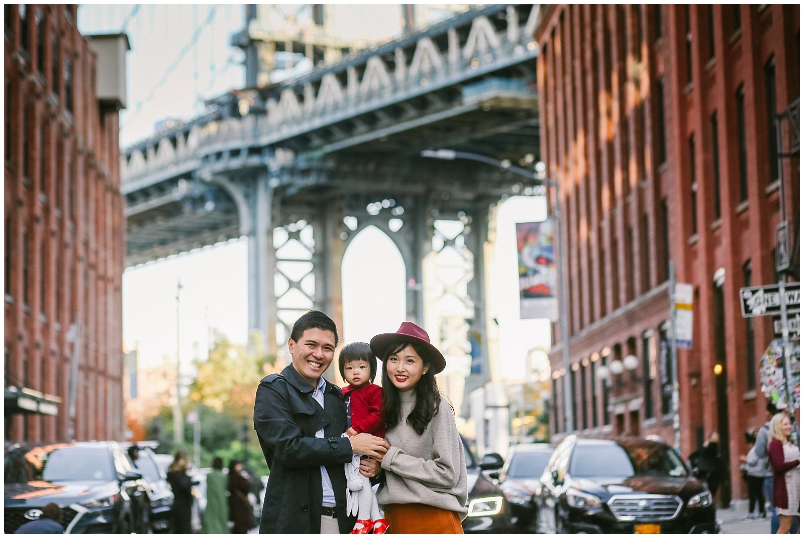 family smiling in front of Manhattan Bridge in DUMBO Brooklyn | Helena Woods nyc family photographer