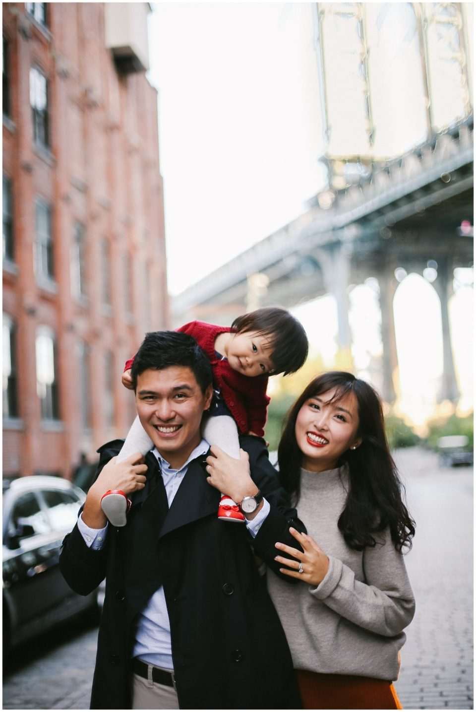 family smiling on water street overlooking Manhattan Bridge in Brooklyn NYC