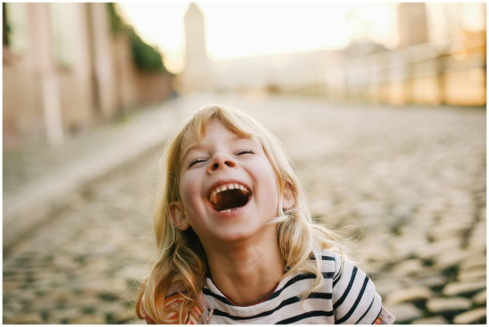 kid laughing from a funny family photography prompt