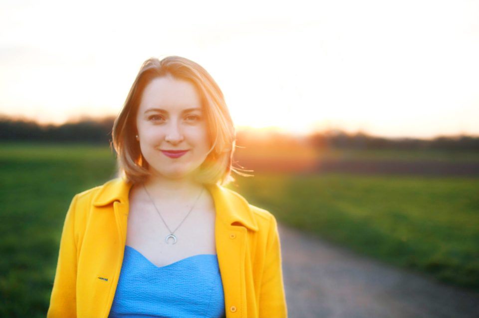 Helena Woods in yellow coat surrounded by golden light