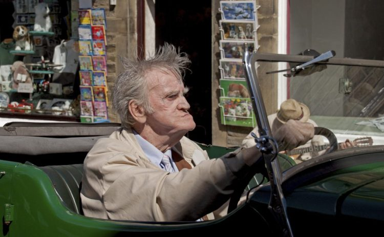 Vintage car and driver Haworth village Yorkshire