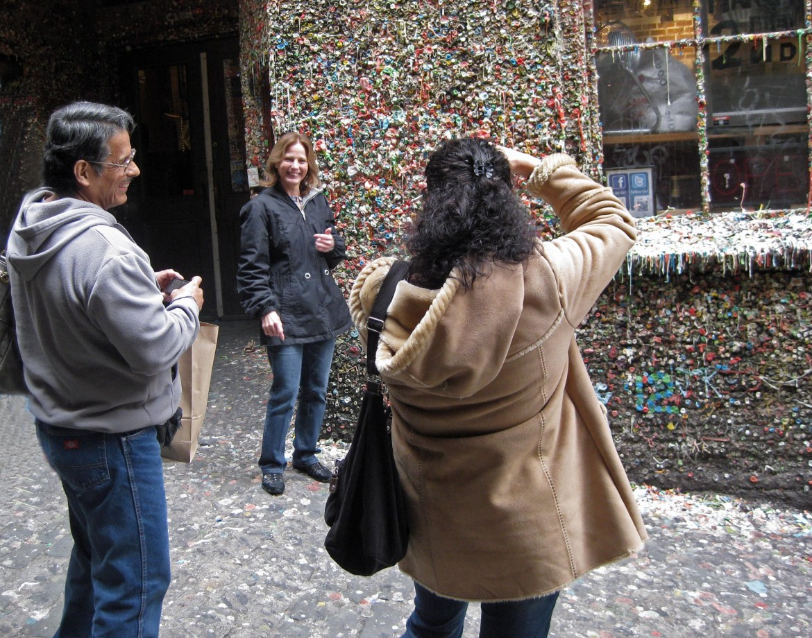 Tourists take turns, shooting gross-out shots at Seattle's Gum Wall. Photo copyright: Helen Holter