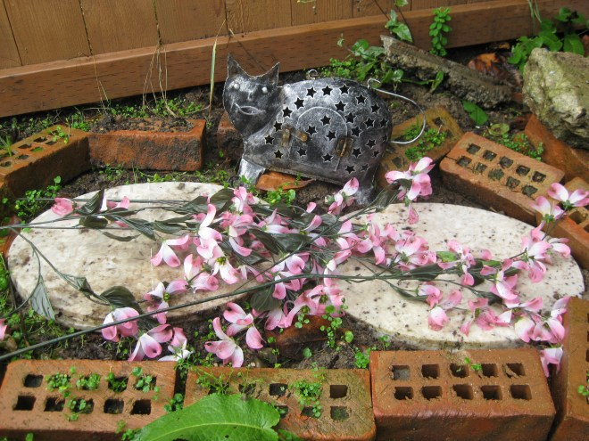Honey and Pepper's graves are marked with recycled things: 1941 bricks, granite oval slabs, and a cast-off cat made of metal, left by the previous homeowner.