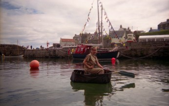 Helen floating in the harbour in a modern coracle