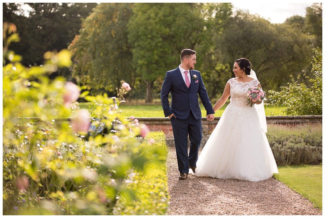 Iscoyd Park Photography bride and groom walking through the gardens