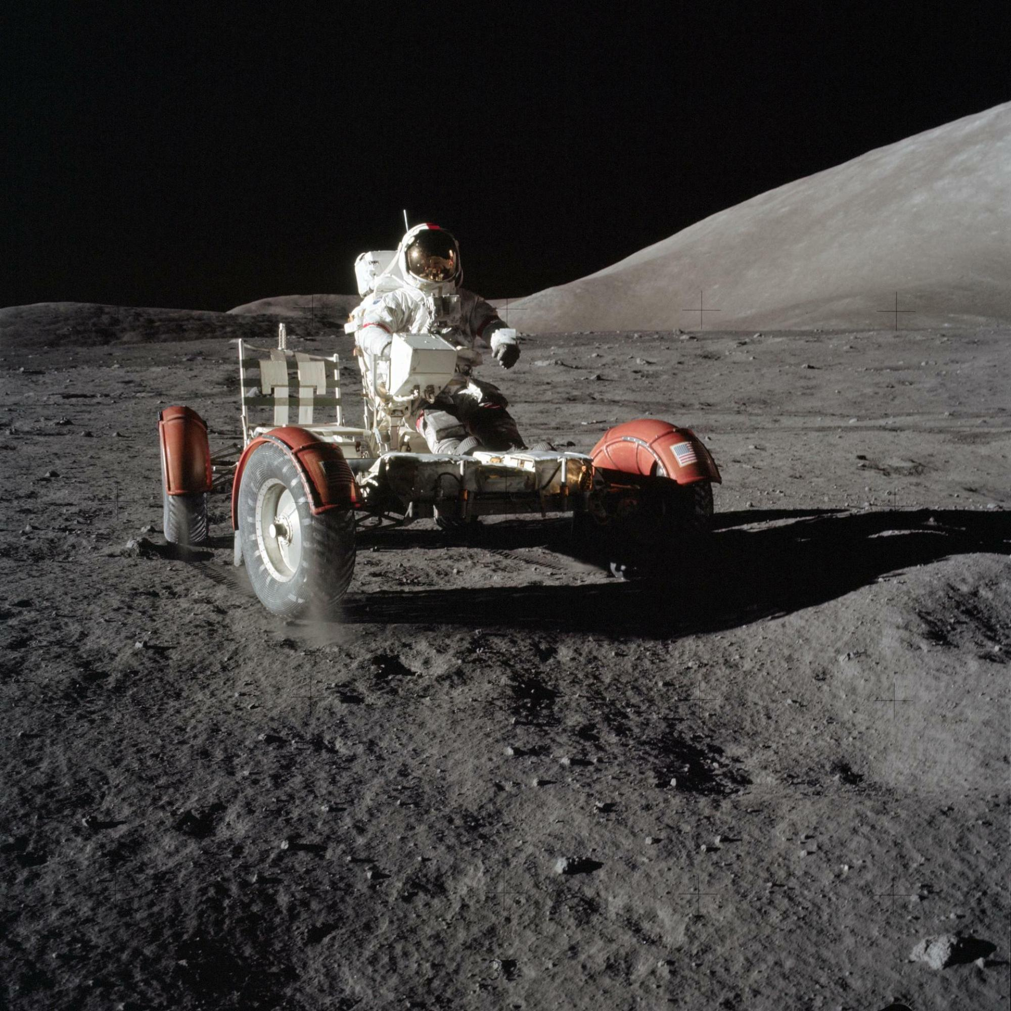 Astronaut Eugene Cernan sits on a barebones Lunar Roving Vehicle during Apollo 17 in 1972. After lowering it from the Lunar Module and unfolding it, astronauts had to raise the seats and install equipment like communications antennae. In this image, the astronauts have not finishing loading equipment onto the LRV.