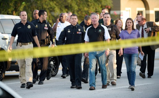 Orlando Mayor Buddy Dyer, center right, and Orlando Police Chief John Mina, center left, arrive to a news conference after a multiple shooting at a nightclub in Orlando, Fla., Sunday, June 12, 2016. (AP Photo/Phelan M. Ebenhack)