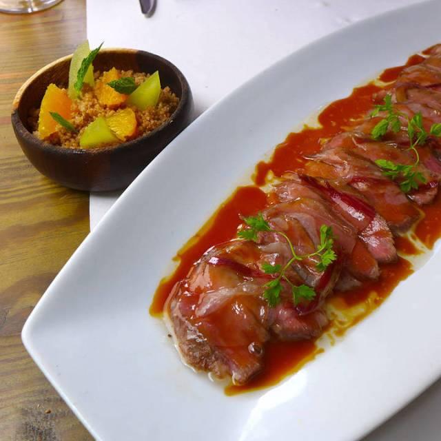 Løvtynne ibericosvin-skiver med smeltet spekeskinke på toppen servert med couscous med appelsin, eple, kanel, kardemomme