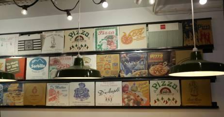 Kult interiør med gamle pizzaesker på veggen.