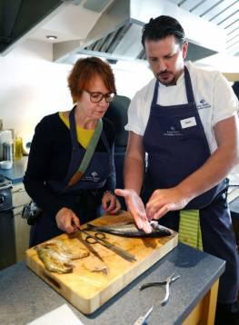 Kokkene på skolen lærer oss hvordan vi skal filitere fisken.