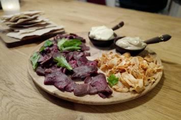 Badstuerøkt reinsdyr med flatbrød, pastinakkchips, rømme og majones av steinsopp og sort hvitløk.