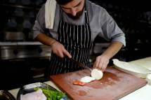 Kokken skjærer tynne skiver av løk.
