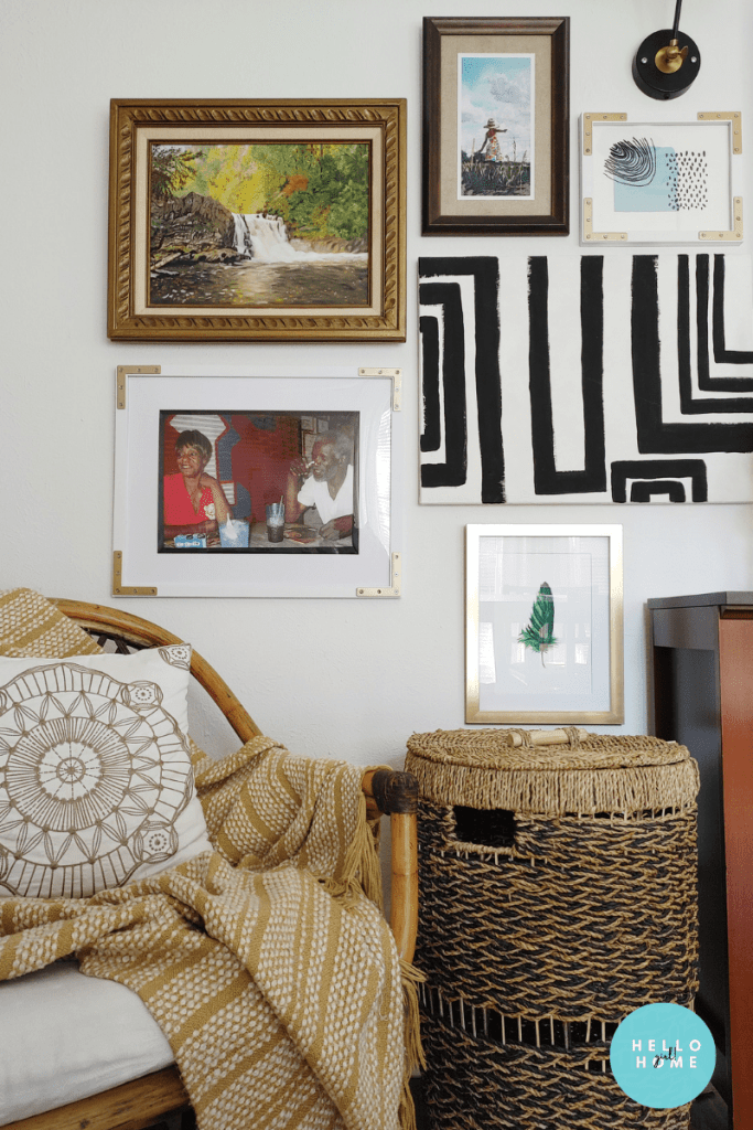 Gallery wall with my parents portrait, a rattan chair, and a basket that hides a paper shredder
