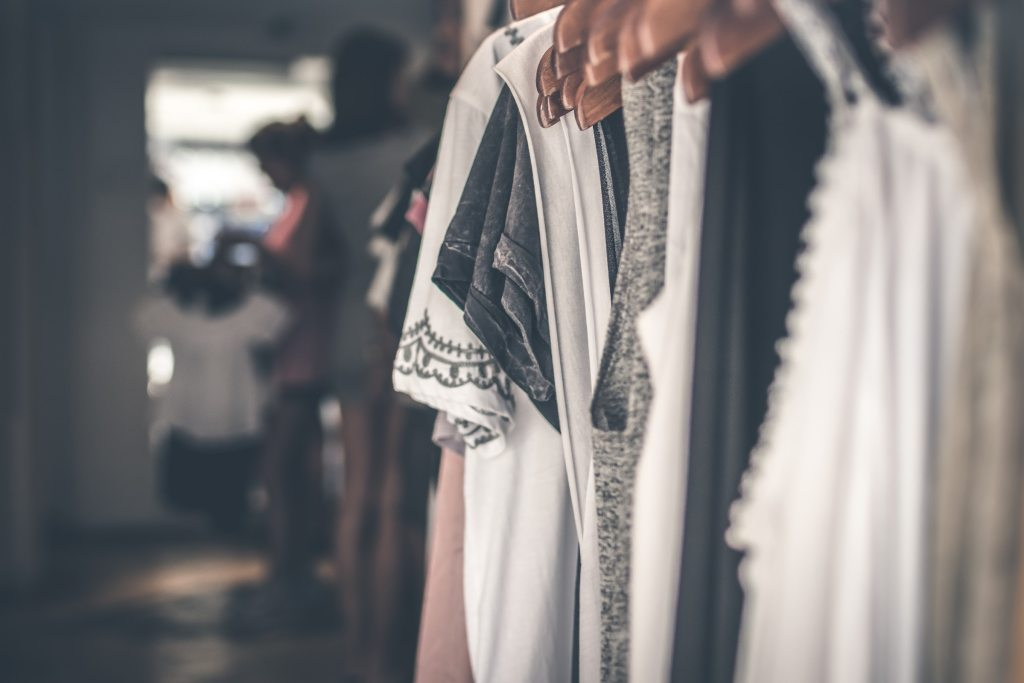 organizing a closet with white and gray shirts on wooden hangers